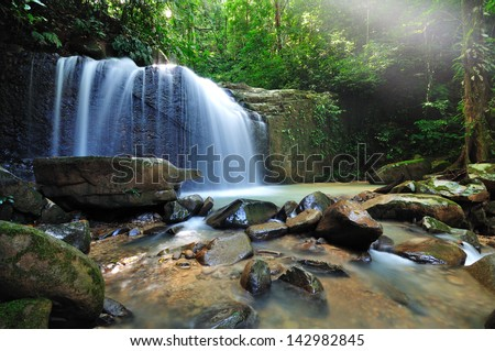 Waterfall in the jungle with early morning rays - stock photo