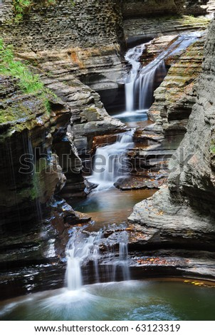 Waterfall in woods with rocks and stream in Watkins Glen state park in New York State - stock photo