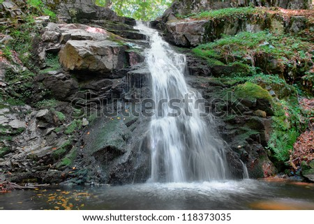 waterfall into forest long exposure background - stock photo