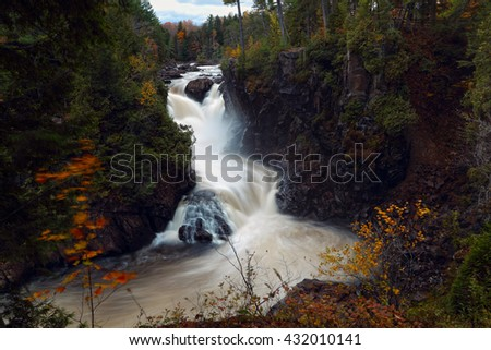 Waterfall landscape in Canada.Scenic Waterfall.Autumn in Canada. Current water.  Stream water. Waterfall landscape in Canada.The red maples leaves frame this beautiful waterfall. - stock photo