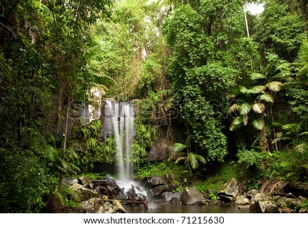 Waterfall making its way into a pond in the rainforest - stock photo
