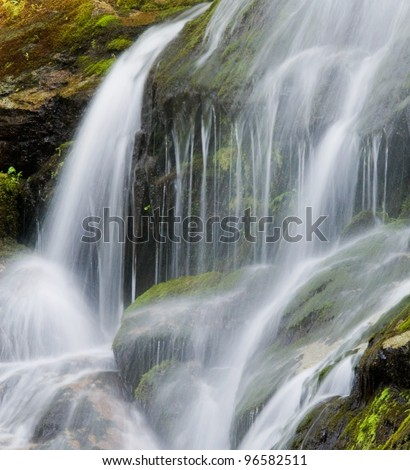 Waterfall on Lichen-covered Rock - stock photo