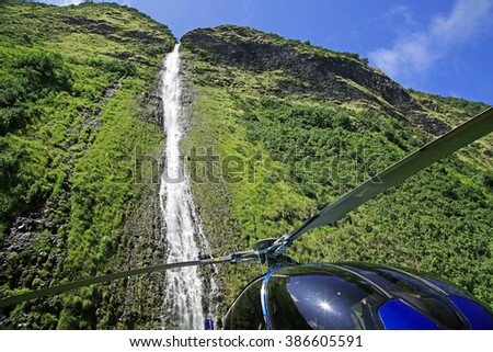 Waterfall on the Kohala Coast of the Big Island of Hawaii (and the helicopter that landed right in front of it) - stock photo