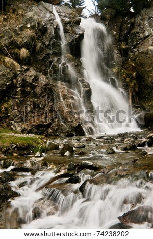 Waterfall over rocks with moss and lichens.  Beautiful place in the Carpathians during a rainy spring day - stock photo