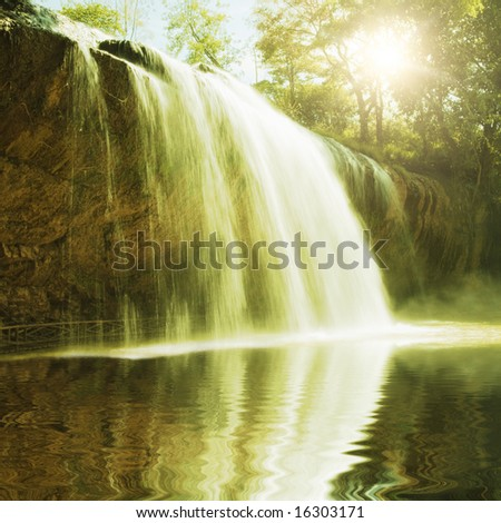 Waterfall pool in rain forest and sunlight - stock photo