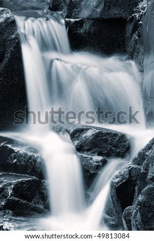 Waterfall rushing down the rocks, blue toning - stock photo