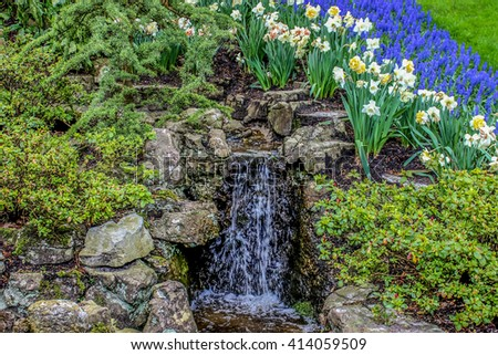 Waterfall small among the greenery and flowers. Nature scenic environment of water and greenery. - stock photo