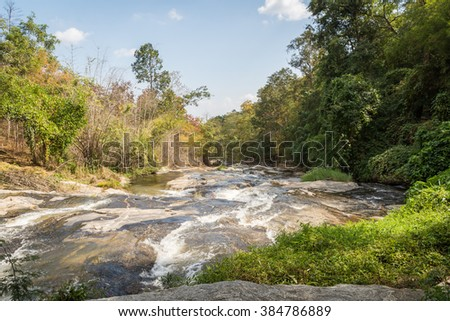 waterfall summer landscape misty morning on the river. - stock photo
