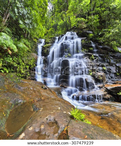 Waterfall valley near Wentworth falls in Blue Mountains, Australia. Low point view towards Empress falls cascade in wet weather - stock photo