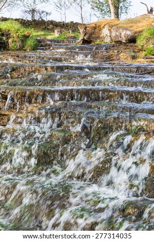 Waterfall with a creek in a pasture in the spring - stock photo