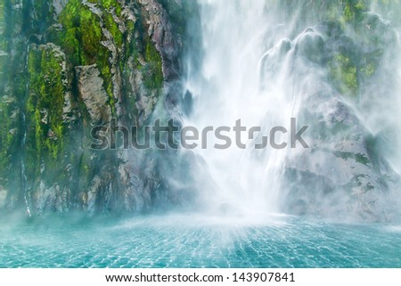 Waterfall with fluffy stream fall on the sea, Milford Sound, Southern Island, New Zealand - stock photo