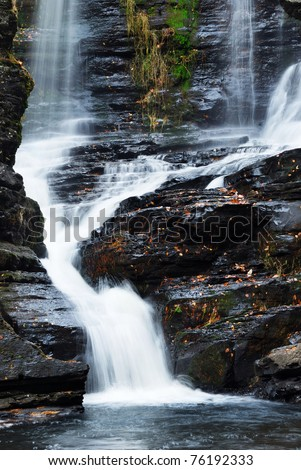 Waterfall with trees and rocks in mountain in Autumn. From Fulmer Falls Pennsylvania Dingmans Falls. - stock photo