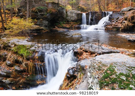Waterfall with trees and rocks in mountain in Autumn. From Pennsylvania Dingmans Falls. - stock photo