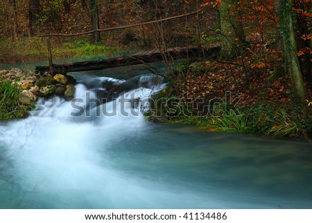 Waterfalls in autumn in the mountains and wooden bridge