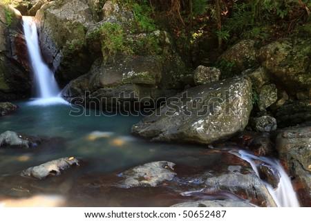 Waterfalls into and out of a pool in the El Yunque rainforest in the Caribbean National Forest, Puerto Rico - stock photo