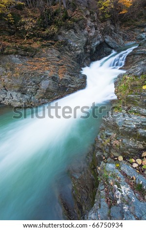 Waterfalls on Rocky Stream, Running Through Autumn Mountain Forest (long time exposure) - stock photo
