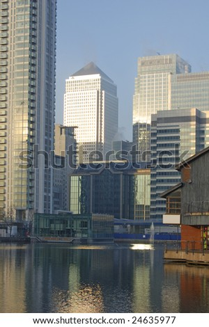 Waterfront buildings at South Dock and Canada Square office towers at Canary Wharf, London, England - stock photo