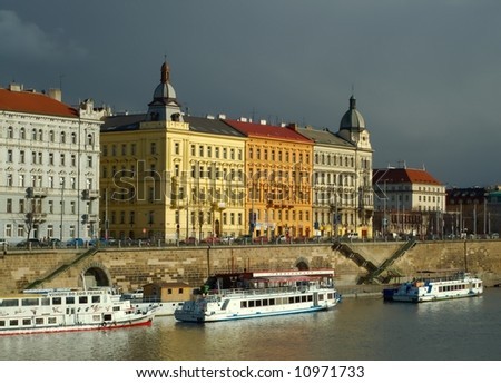 Waterfront buildings in Prague in the evening sunlight, with heavy rain clouds