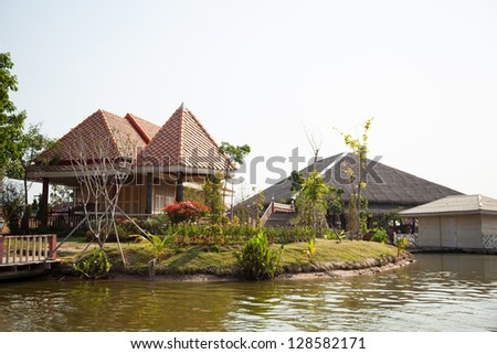 Waterfront home gardening in small yard. Water on the outside. - stock photo