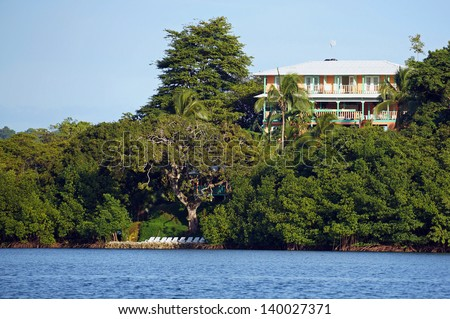 Waterfront hotel with lush vegetation on a tropical island of the Caribbean sea, Bastimentos, Panama, Central America - stock photo