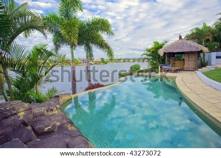 Waterfront Mansion with Pool and Bali hut overlooking the canal - stock photo