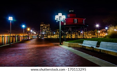 Waterfront promenade and lighthouse at night in the Inner Harbor, Baltimore, Maryland. - stock photo