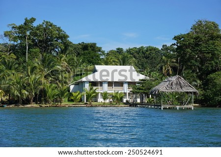 Waterfront property with a Caribbean house and thatched hut over the sea, Bocas del Toro, Panama, Solarte island - stock photo