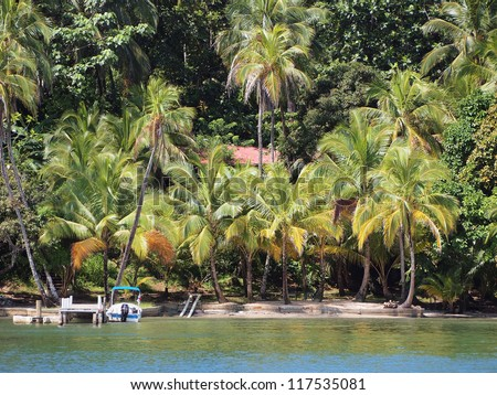 Waterfront property with boat at dock and lush tropical vegetation on an island in the Caribbean sea, Panama - stock photo