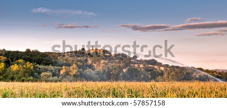 Watering a field of maize with Italian hill top village in background - stock photo