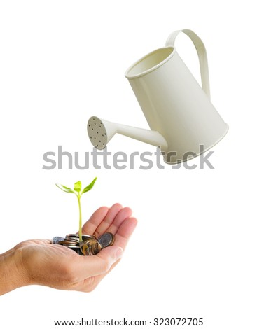 Watering a tree growing from coins on hand - stock photo