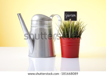 watering can and house plant isolated on yellow - stock photo