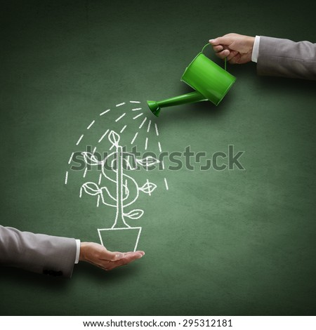 Watering can and money tree drawn on a blackboard concept for business investment, savings and making money - stock photo