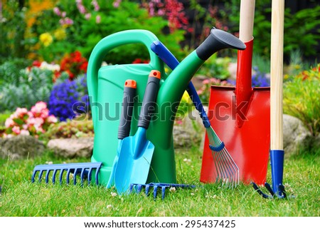 Watering can and tools in the garden - stock photo