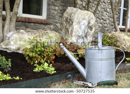 Watering can and trowel nest to landscape. Shallow depth of field. - stock photo