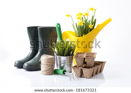 watering can, garden boots and garden plants - stock photo