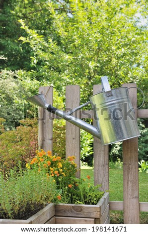 watering can hanging on a wooden fence in a garden
