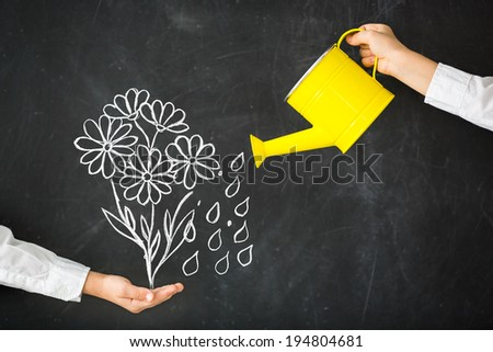 Watering-can in hand against blackboard - stock photo
