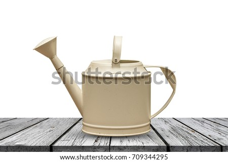 Watering can on wood table with white background