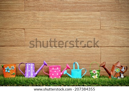 watering cans and pails on green grass with wood background - stock photo