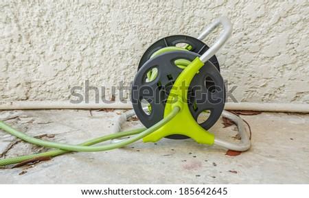 Watering garden hose on cement floor - stock photo