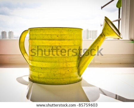 Watering pot the sun shines and the shadows on a white background - stock photo