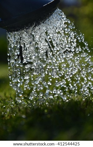 Watering the lawn after mowing the home lawn mower. Watering can with rainwater. Drops of water falling on the grass. Spring and summer cover a period. Sunny day and growing vegetation.Garden. - stock photo