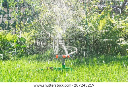 Watering the lawn in the garden - stock photo