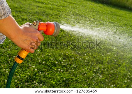 Watering the lawn with spray gun - stock photo