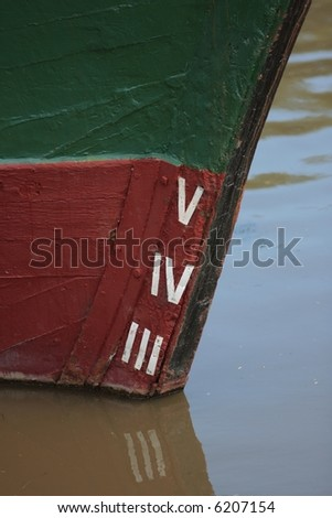 Waterline marks on an old wooden ship, moored in murky river water.