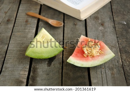Watermelon and melon leftovers with wooden spoon and book on gray wooden background - stock photo