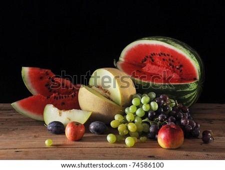 Watermelon and melon with fruit on the table - stock photo