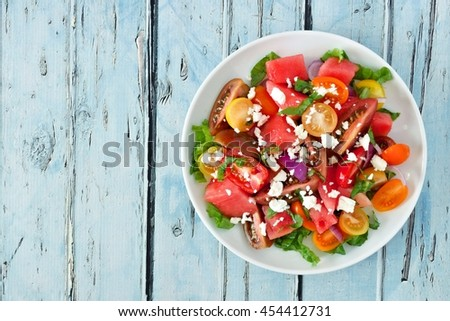 Watermelon and mixed tomato salad with feta cheese, above view on rustic blue wood - stock photo