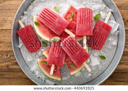 Watermelon and strawberry popsicles on ice filled tray - stock photo