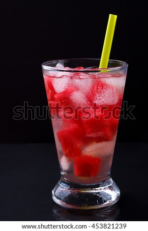 Watermelon cocktail in a glass on black stone background